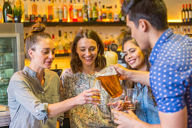 Young Man Pouring Drinks For Girls in a Bar stock photo