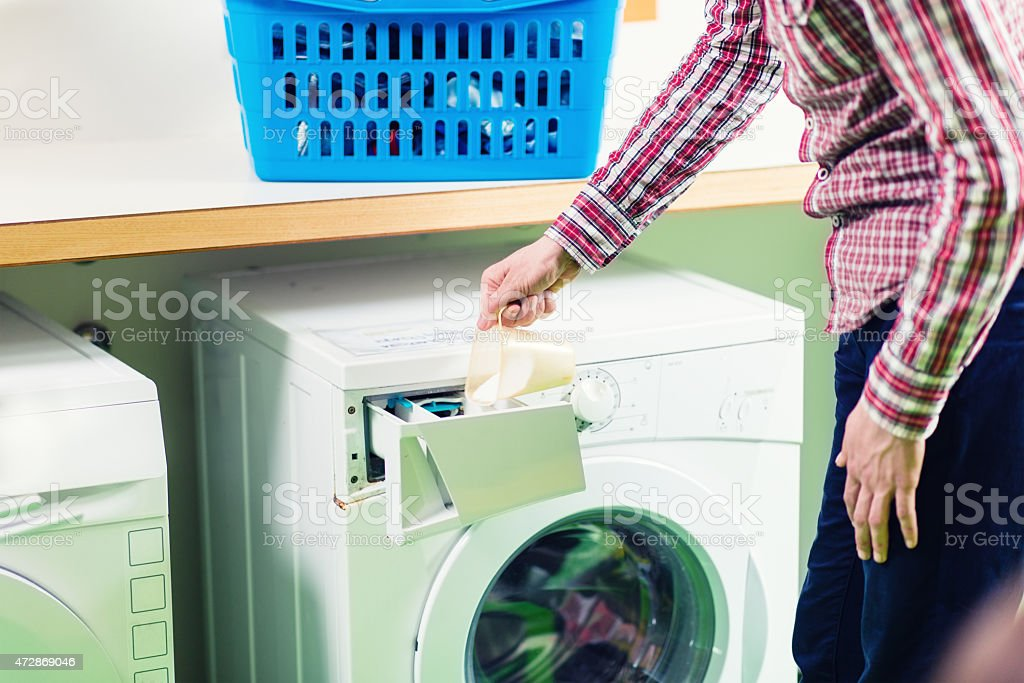 Young Man Pouring Laundry Detergent Royalty Free Stock Photo