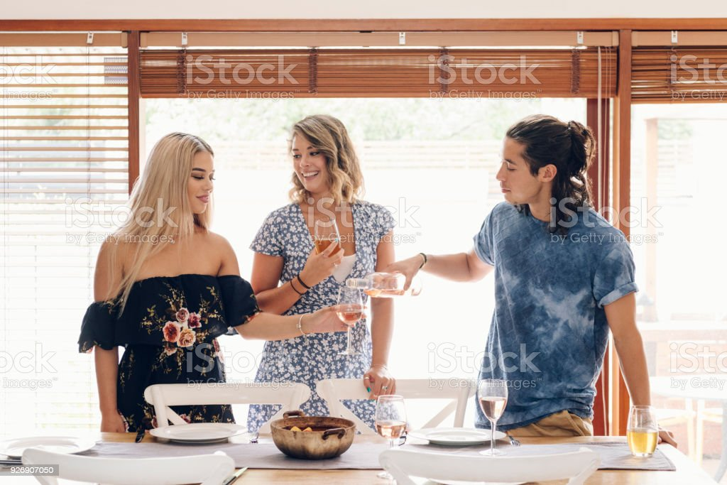 Young man pouring wine for two young women at dining table - Stock image . f291b1b77