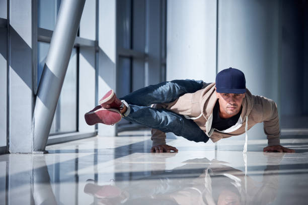 Young man practices yoga asana indoors in the empty hall of airport stock photo