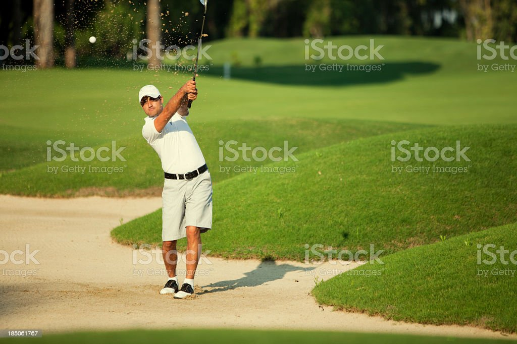 Young man practicing his swing in green golf course stock photo