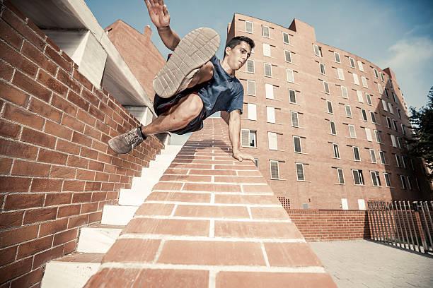 junger mann üben parkour- in der stadt - parkour stock-fotos und bilder