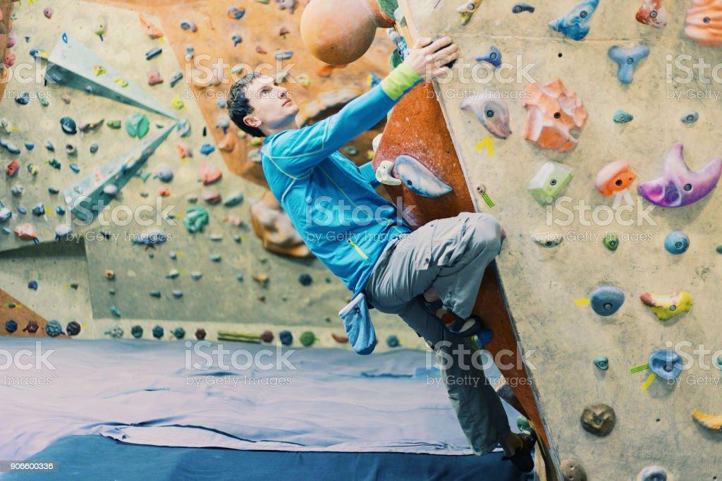 Junger Mann Klettern auf einer Felswand in Innenräumen zu üben. – Foto