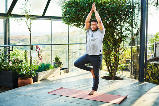 Young man in sportswear practicing the tree pose on an exercise mat during a yoga session in a bright modern studio