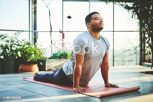 Mid adult man practicing Upward Facing Dog Pose. Handsome fit male is doing yoga on exercise mat. He is in sportswear.