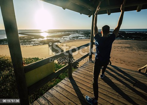 1088451256 istock photo Young man practicing yoga at the pier with the beach of Sanlucar de Barrameda in the background 961976136