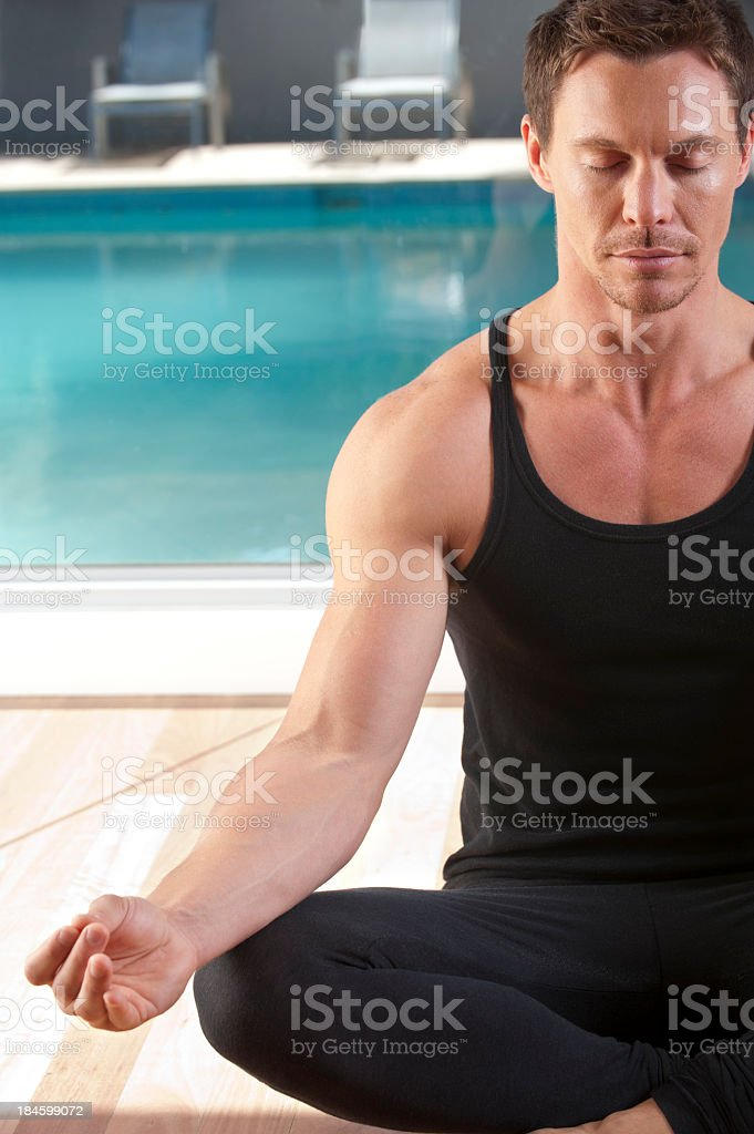 Young man practicing yoga in a sun filled room royalty-free stock photo