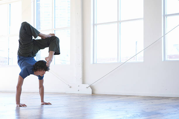 Young man practicing yoga, performing handstand stock photo