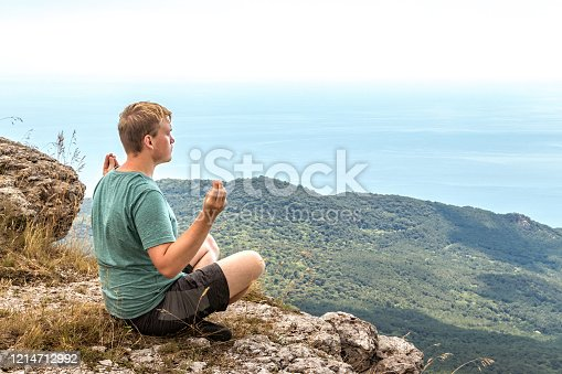 Young man practicing yoga pose sitting on the rocky peak