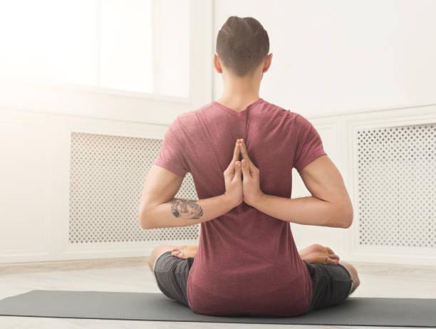 junger mann, yoga zu praktizieren, reverse gebet darstellen - ruhegebet tattoo stock-fotos und bilder
