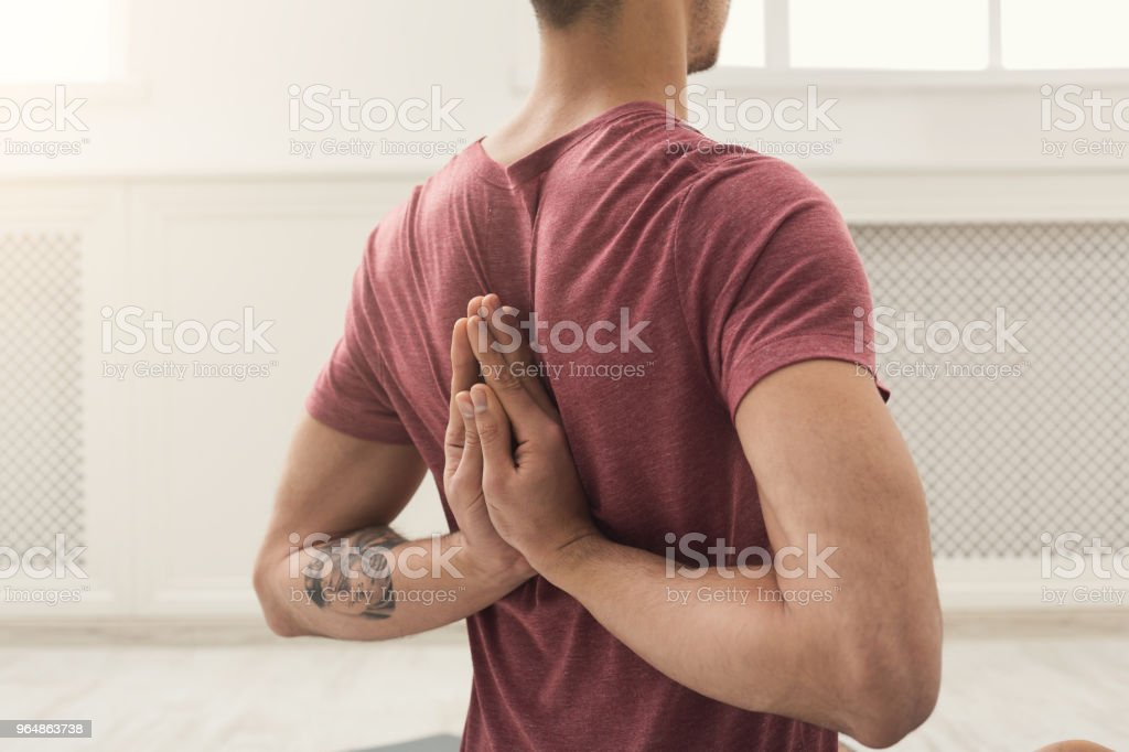 Young man practicing yoga, Reverse Prayer Pose royalty-free stock photo