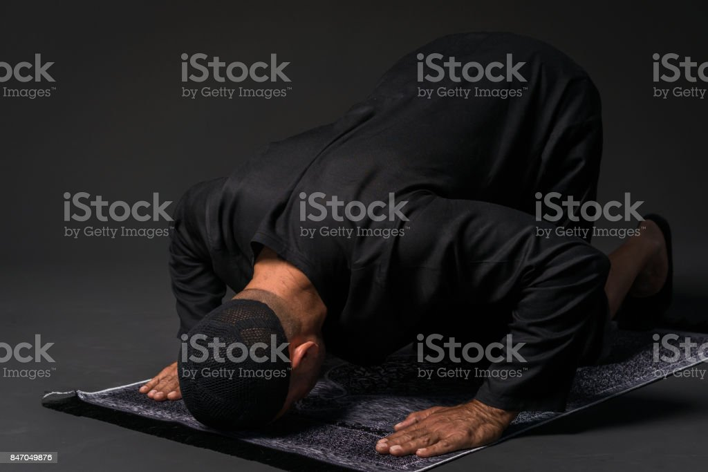 Young man praying  over black backround stock photo