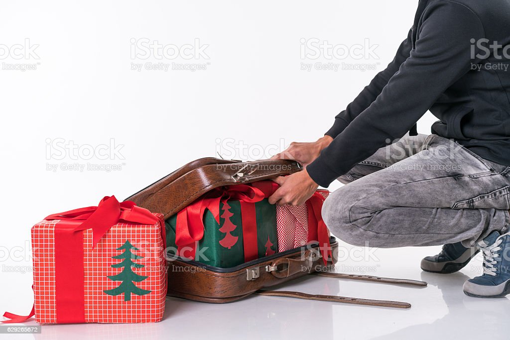 young man prepareing Christmas gifts ın the retro suitcase stock photo