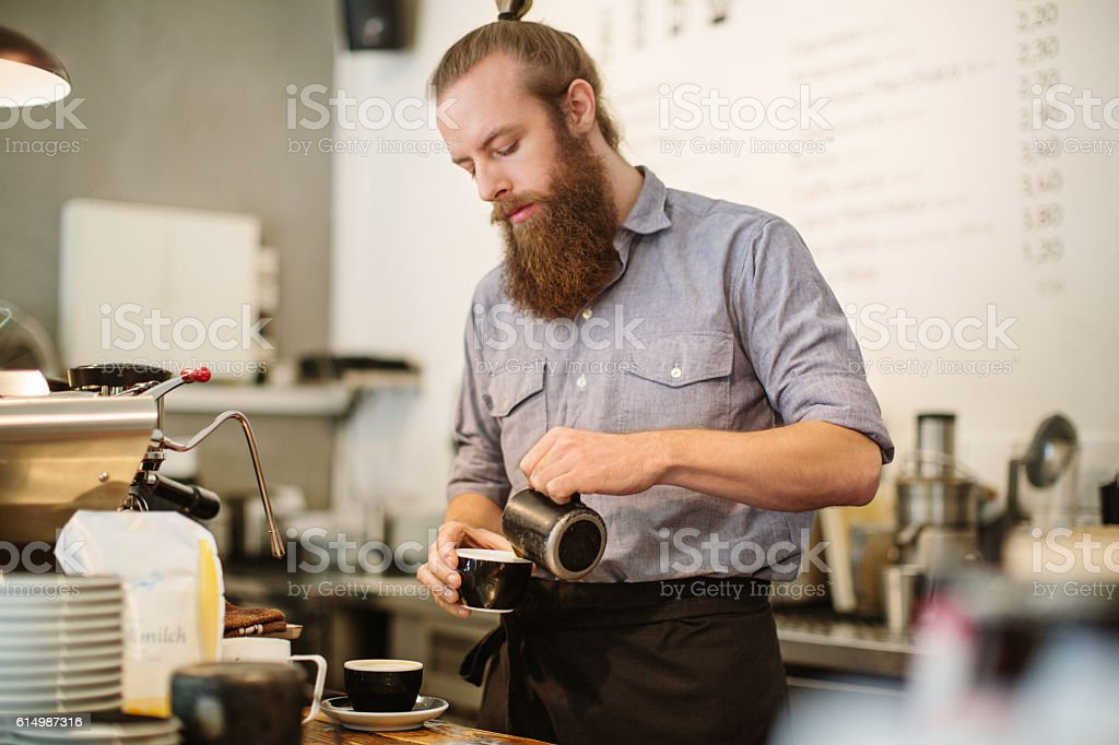 Young man preparing coffee at cafe counter stock photo