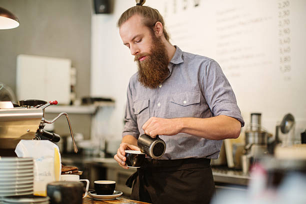 young man preparing coffee at cafe counter - barista stock photos and pictures