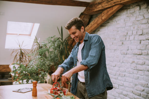 Young man preparing food in the kitchen stock photo