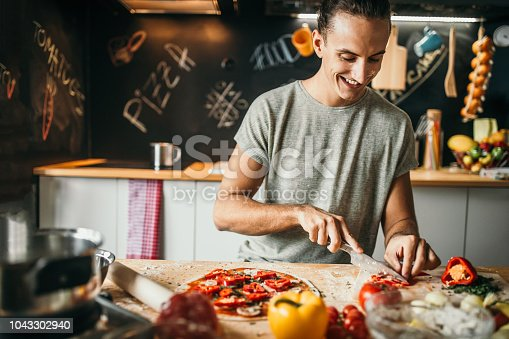 Photo of young man preparing pizza at home