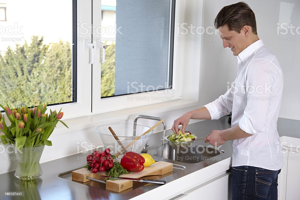 Young man preparing salad in the kitchen royalty-free stock photo