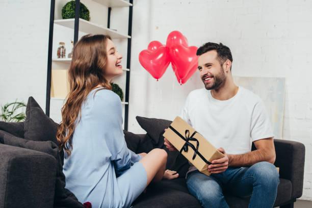 バレンタインの日に若者のガール フレンドに提示のギフト ボックス - ボーイフレンド ストックフォトと画像