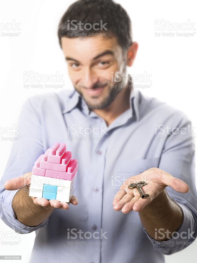 Young Man presenting Miniature House and Key royalty-free stock photo