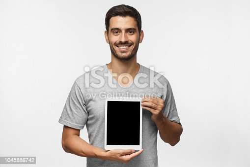 istock Young man presenting vertical blank tablet screen to viewers with smile, copy space for advertisment of goods or app,  isolated on gray background 1045886742