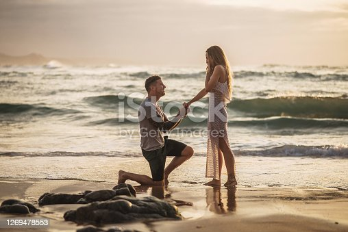 Young man kneeeling, proposing to his girlfriend by the sea