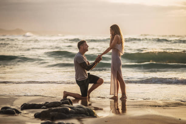 Young man proposing to his girlfriend at a beach stock photo