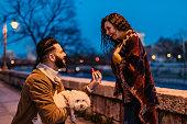Young Caucasian man proposing to his beautiful girlfriend.