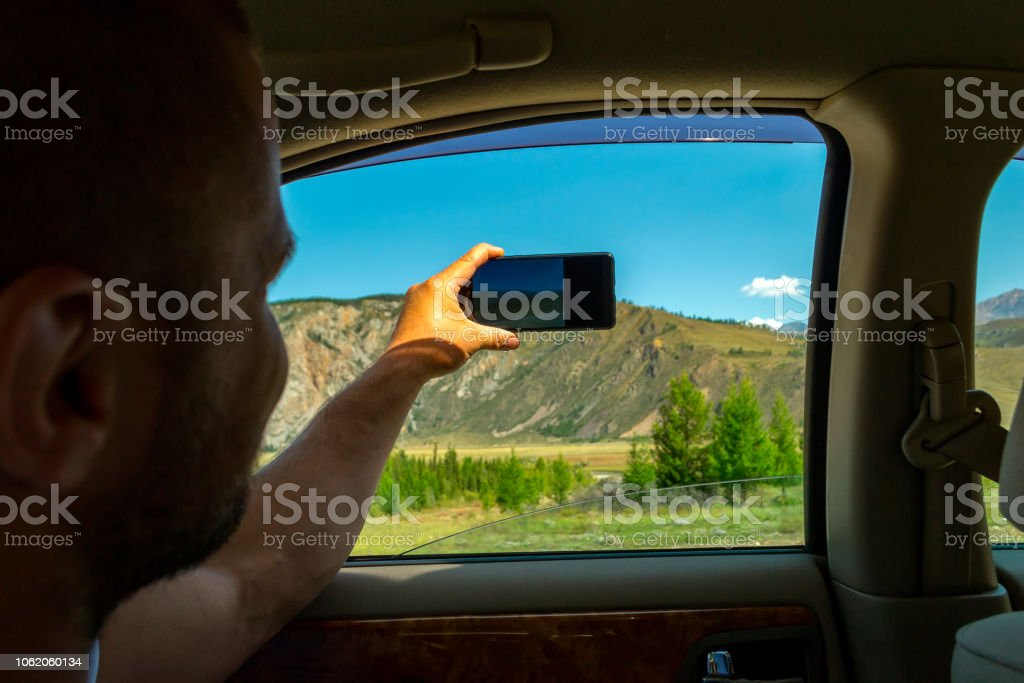 A young man pulling one hairy hand into the open window of a moving car holds a smartphone taking a photo of the mountains in the Altai with blue clear sky on an autumnal summer day during a journey stock photo