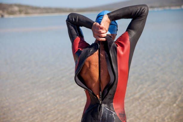 Young man pulling the zipper of a triathlon race suit Young man pulling the zipper of a triathlon race suit wetsuit stock pictures, royalty-free photos & images