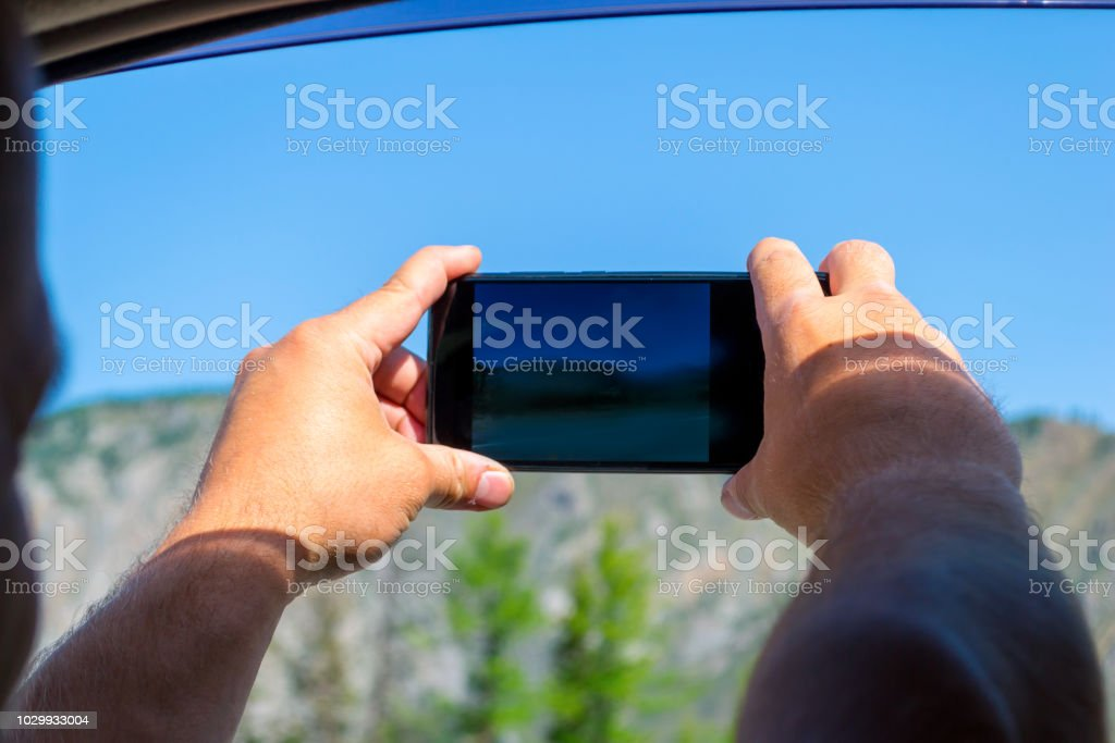 A young man pulling two hairy hands into the open window of a moving car holds a smartphone taking a photo of the mountains in the Altai with blue clear sky on an autumnal summer day during a journey stock photo