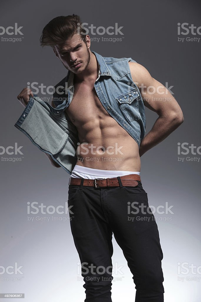 young man pulls his jeans vest stock photo