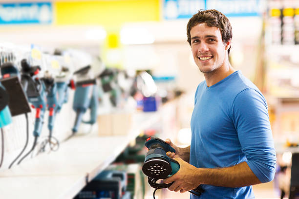young man purchasing hand tool in hardware shop stock photo