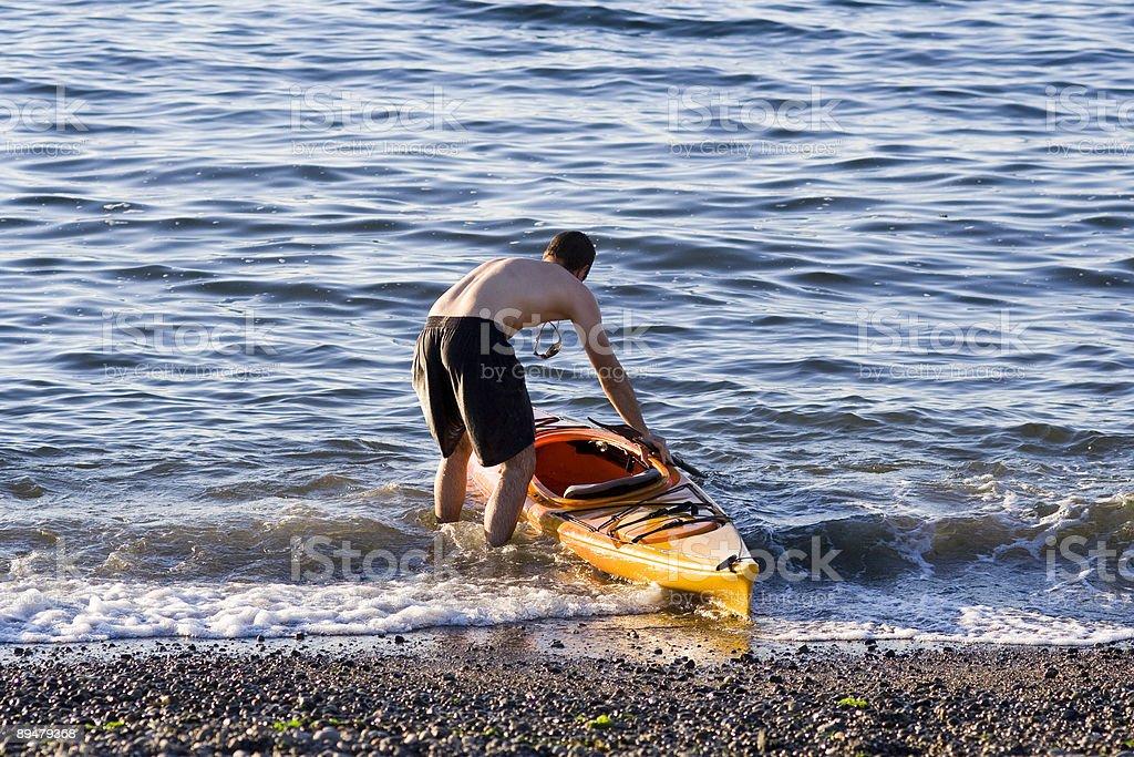 Young man pushing out kayak at sunset royalty-free stock photo