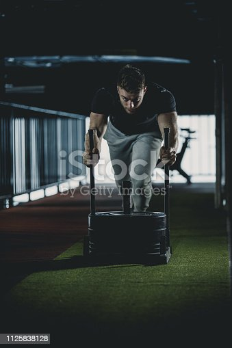 Caucasian young man is pushing weighted sled in the gym.