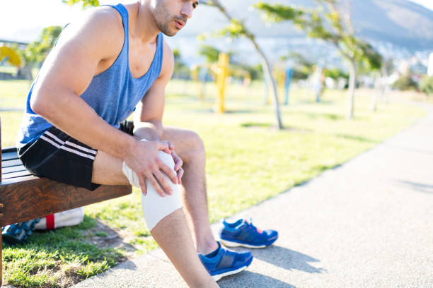 Young man puts support bandage on knee injury sitting in park stock photo