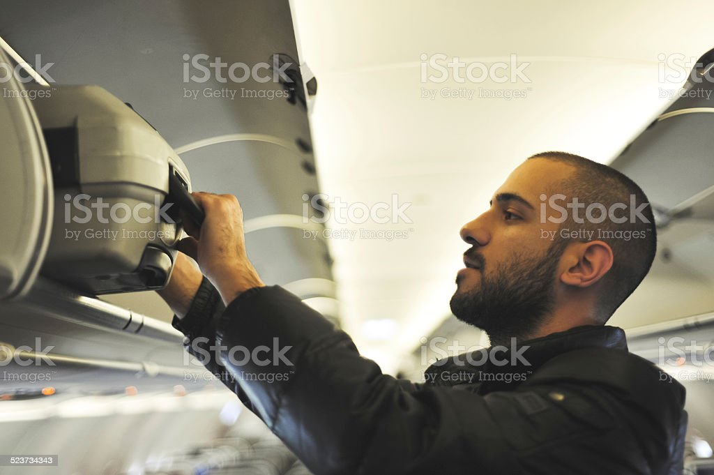 Young man putting a suitcase in an overhead compartment stock photo