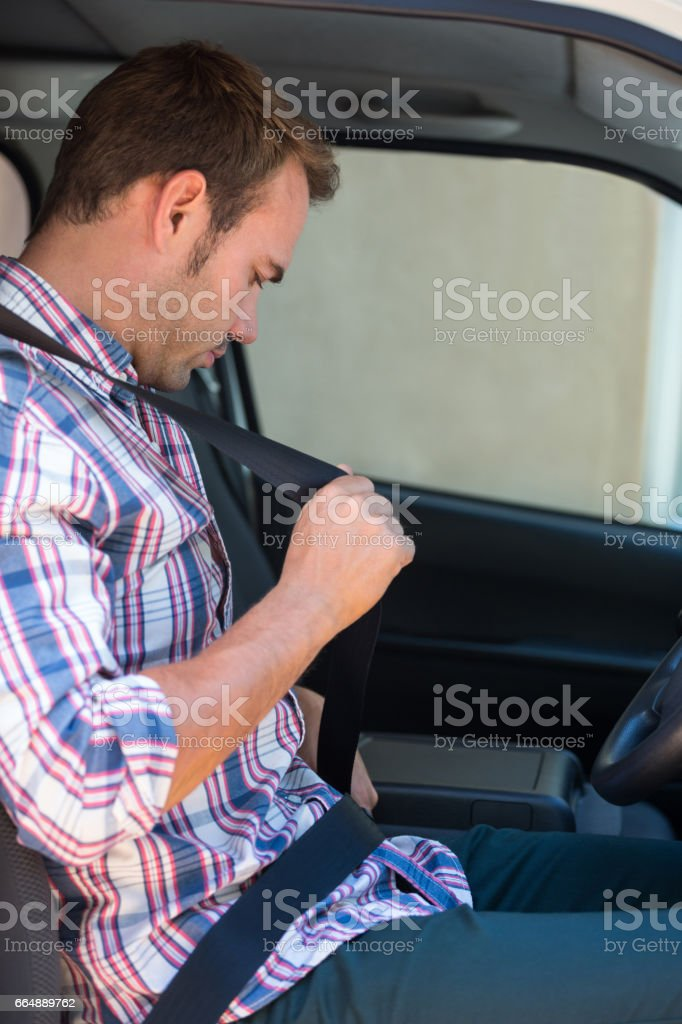 Young man putting on his seat belt foto stock royalty-free