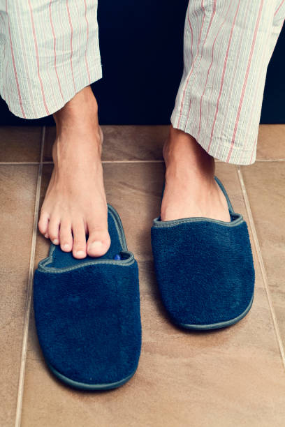 young man putting on or off his slippers stock photo
