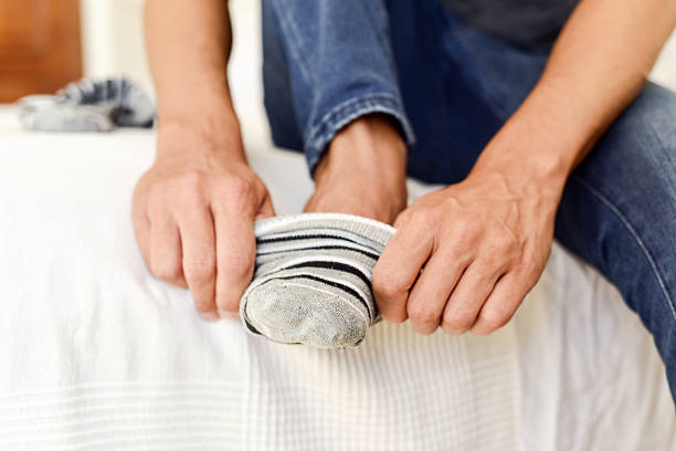 young man putting on or taking off his socks closeup of a young caucasian man sitting on the edge of the bed putting on or taking off a pair of striped socks undressing stock pictures, royalty-free photos & images