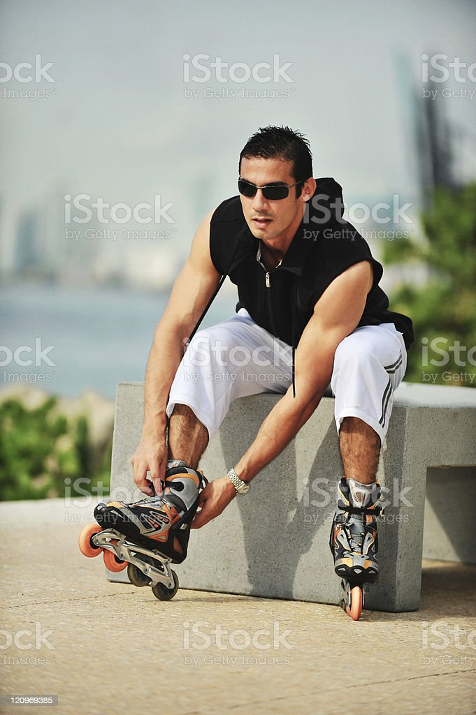 Young man putting on rollerblades royalty-free stock photo