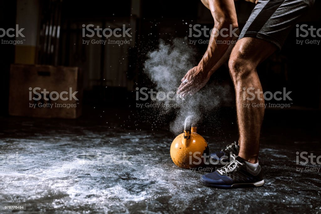 Young Man Putting On Sports Chalk For Lifting Barbell stock photo