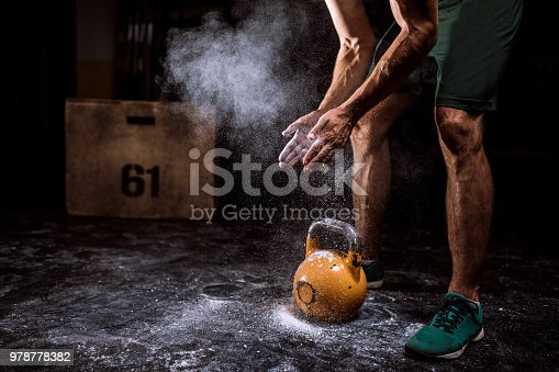 944655208 istock photo Young Man Putting On Sports Chalk For Lifting Barbell 978778382
