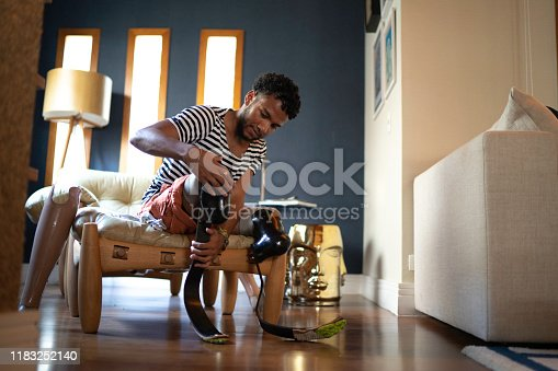 Young man putting prosthetic leg at home