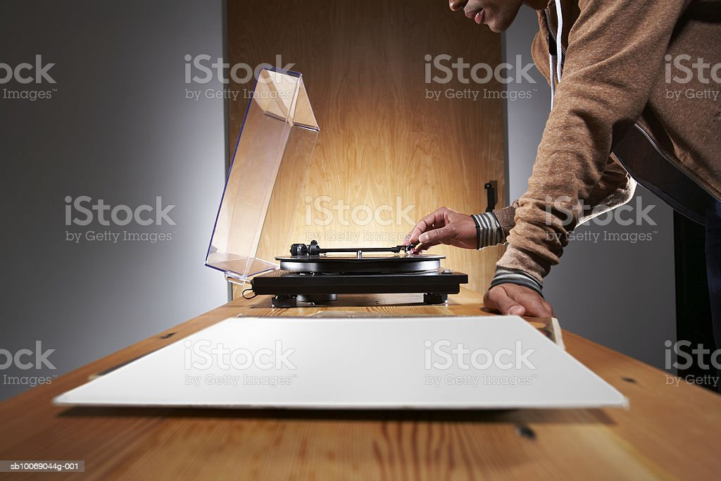 Young man putting stylus on record player, mid section royalty-free stock photo