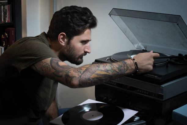 Young man putting the cartridge record player on the vinyl - foto stock