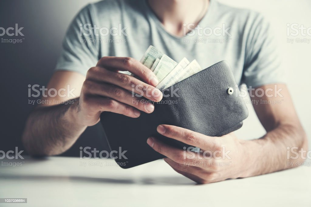 young man qounting money on wallet
