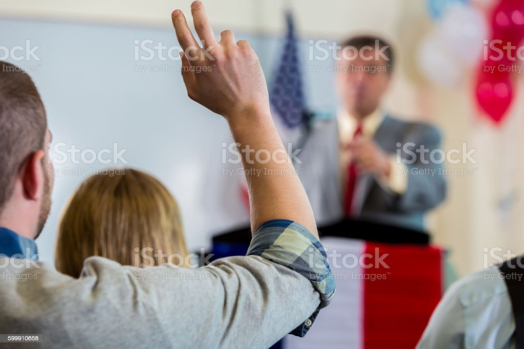 Young man raising hand during political town hall meeting stock photo