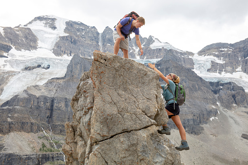 Young man reaches for sibling's hand up mountain peak