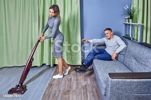 Young man reaching for woman vacuuming